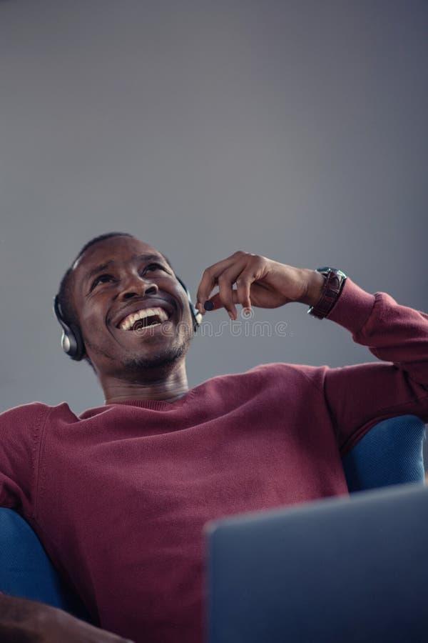 Emotionele donkere gevilde mannelijke freelancer die voltooid project met succes vieren stock fotografie