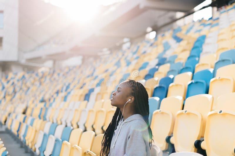 Emotionele foto van het vrij Afro-Amerikaanse meisje die de gelijke op het stadion waarnemen Zonovergoten stock fotografie