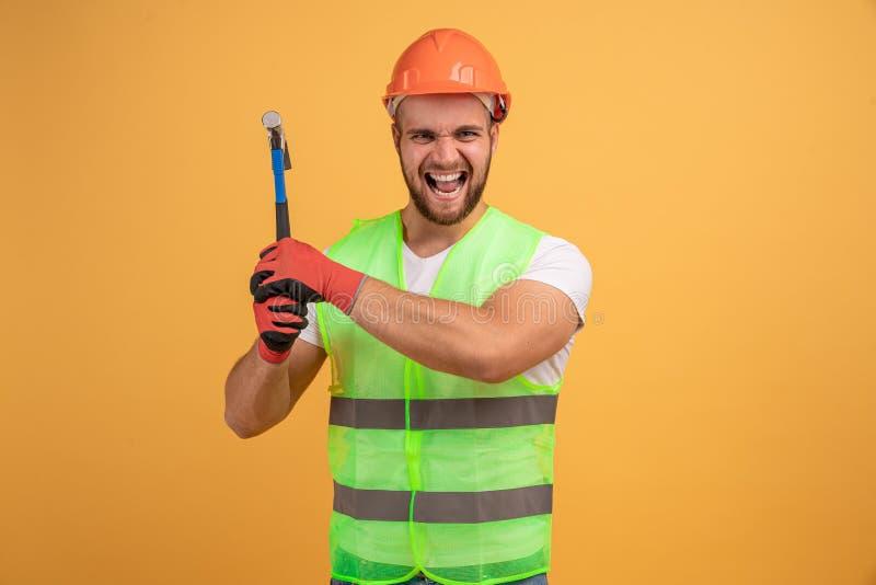 Emotionele handyman houdt hamer vast met beide handen, klaar voor werk, draagt oranje beschermende helm, tijdelijk werkslijtage,  royalty-vrije stock foto's