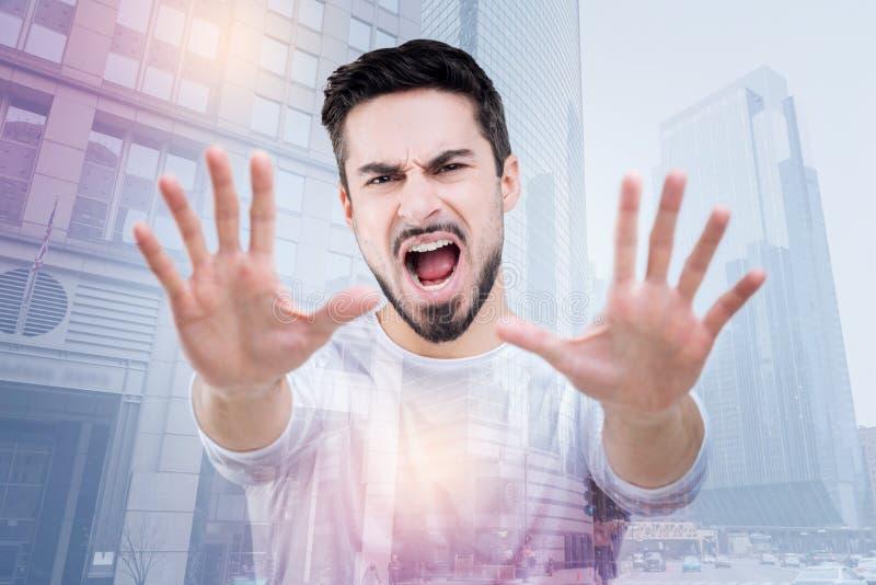 Emotionele jonge mens die naar een tandarts en het schreeuwen verwerpen te gaan royalty-vrije stock foto