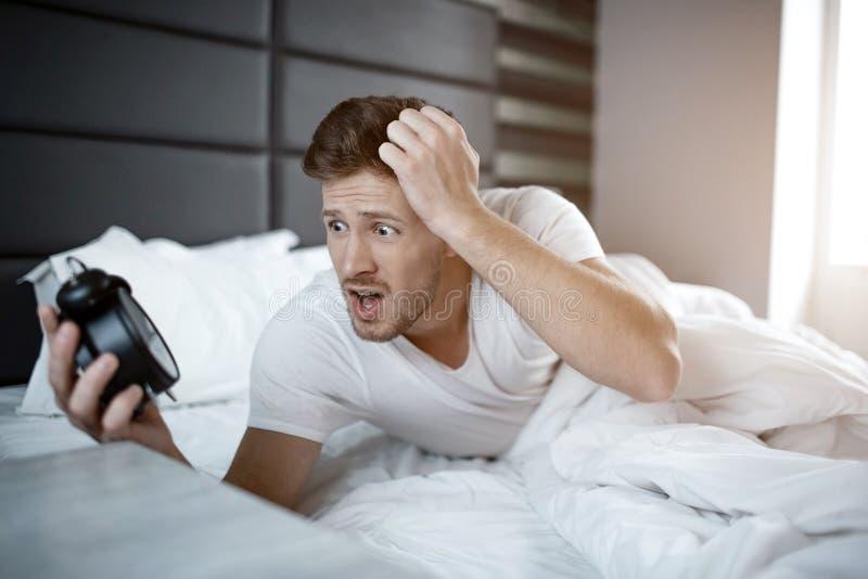Emotionele jonge mens op bed in vroege ochtend Hij versliep zich De klok van de kerelgreep en bekijkt doen schrikken het royalty-vrije stock afbeelding