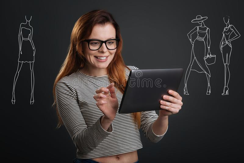 Emotionele jonge ontwerper die terwijl het creëren van schetsen in haar tablet glimlachen stock foto