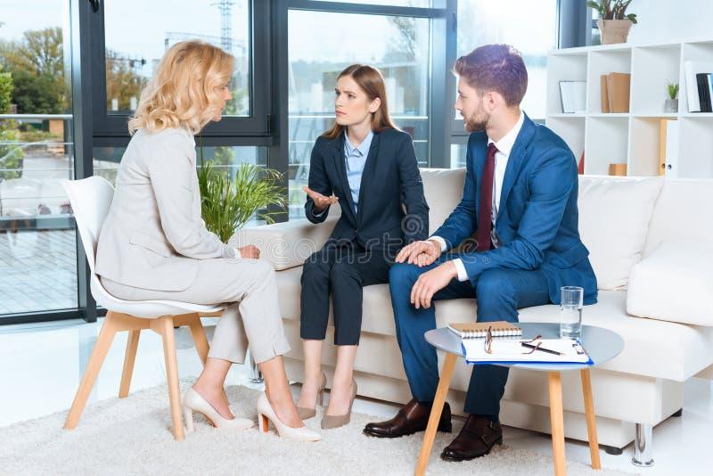 emotionele jonge paar en psycholoog tijdens therapie stock afbeelding