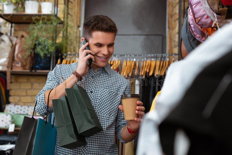 Emotionele jonge prettig nieuws horen en mens die terwijl het bezoeken de kleren winkelen glimlachen stock foto's