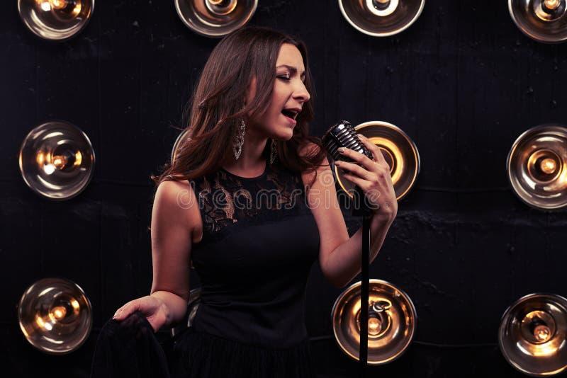 Emotionele jonge vrouw die een retro zilveren studiomicrofoon i houden royalty-vrije stock foto's
