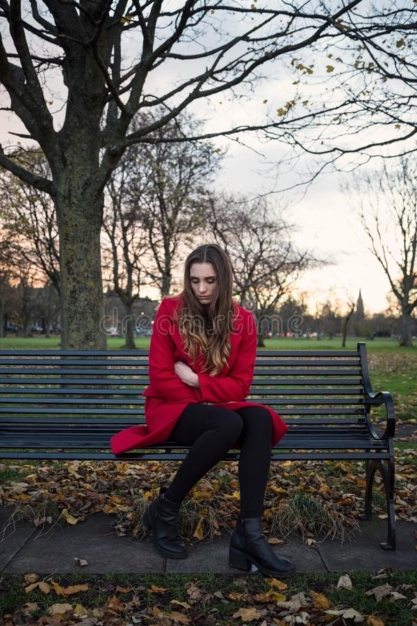 Emotionele jonge vrouwenzitting op een parkbank stock fotografie