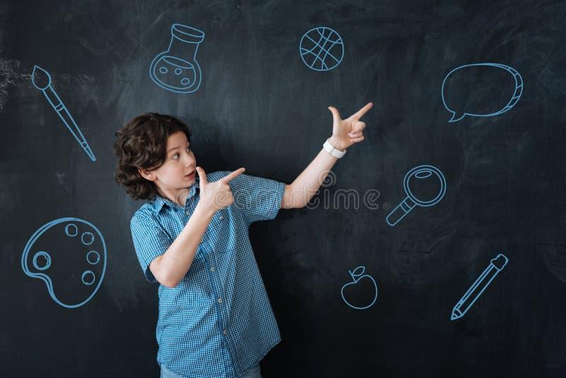 Emotionele jongen die aan de muur richten terwijl het zijn op school royalty-vrije stock afbeelding