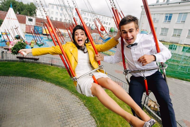 Emotionele jonggehuwden die terwijl het berijden op hoge carrousel in pretpark gillen Expressief huwelijkspaar in Carnaval royalty-vrije stock foto's