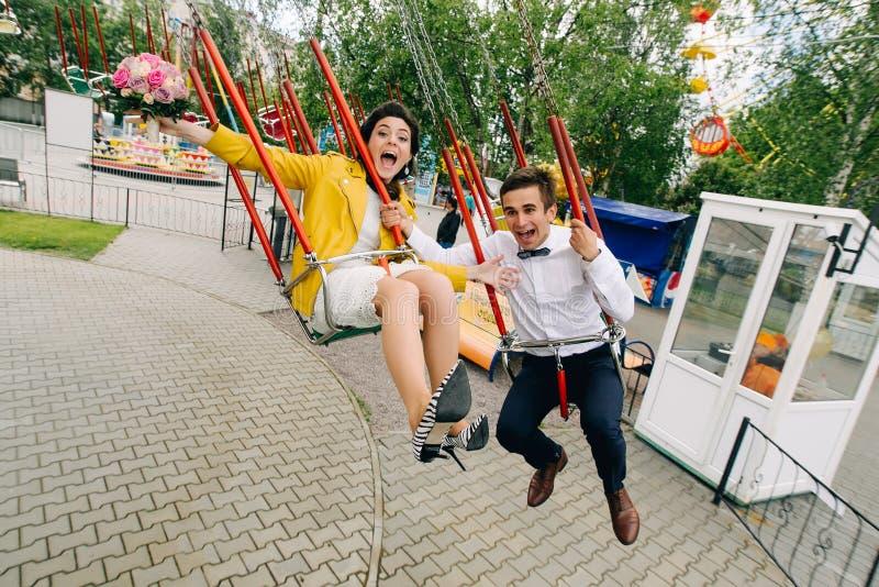Emotionele jonggehuwden die terwijl het berijden op hoge carrousel in pretpark gillen Expressief huwelijkspaar in Carnaval stock afbeelding