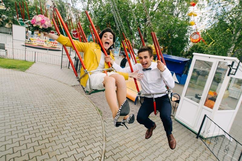 Emotionele jonggehuwden die terwijl het berijden op hoge carrousel in pretpark gillen Expressief huwelijkspaar in Carnaval stock fotografie