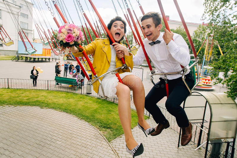Emotionele jonggehuwden die terwijl het berijden op hoge carrousel in pretpark gillen Expressief huwelijkspaar in Carnaval royalty-vrije stock foto