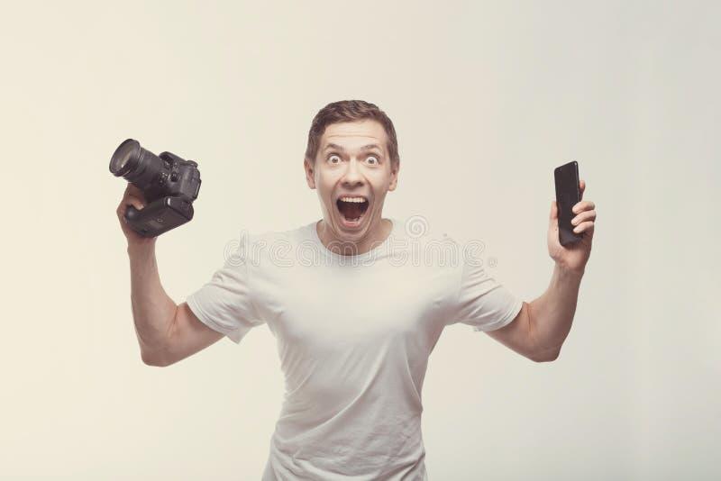Emotionele Mens met camera die op lichte achtergrond wordt geïsoleerd De camera en smartphone van de jonge mensenholding met over royalty-vrije stock afbeeldingen