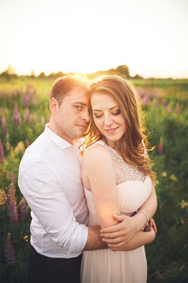 Emotionele mooie bruid die jonggehuwdebruidegom van achter zonsondergang koesteren bij een gebiedsclose-up stock afbeeldingen