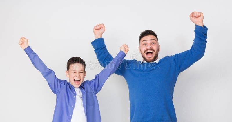 Emotionele opgewekte vader en zoon die voor overwinning toejuichen stock fotografie