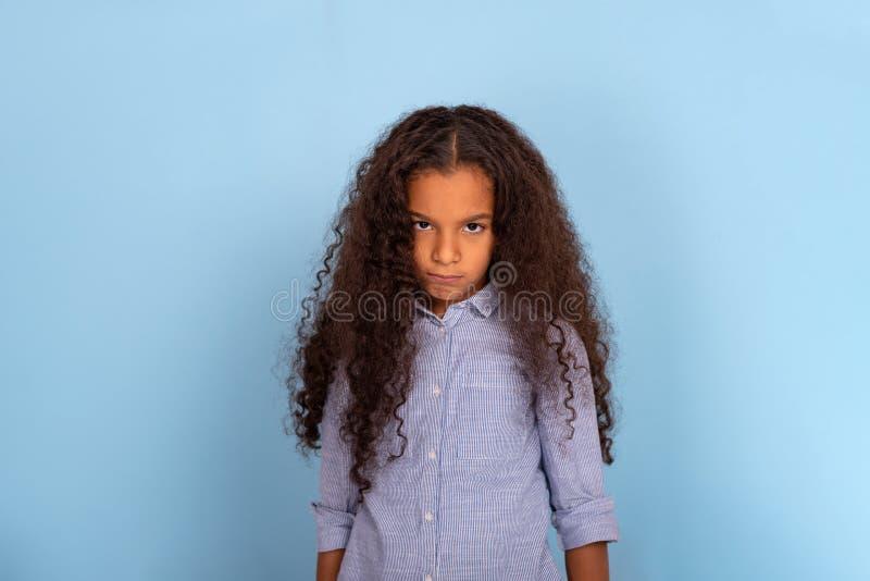 Emotionele portret van de studiotaille het omhoog van mulatta kroes- meisje die blauw overhemd op een blauwe achtergrond met exem stock afbeeldingen