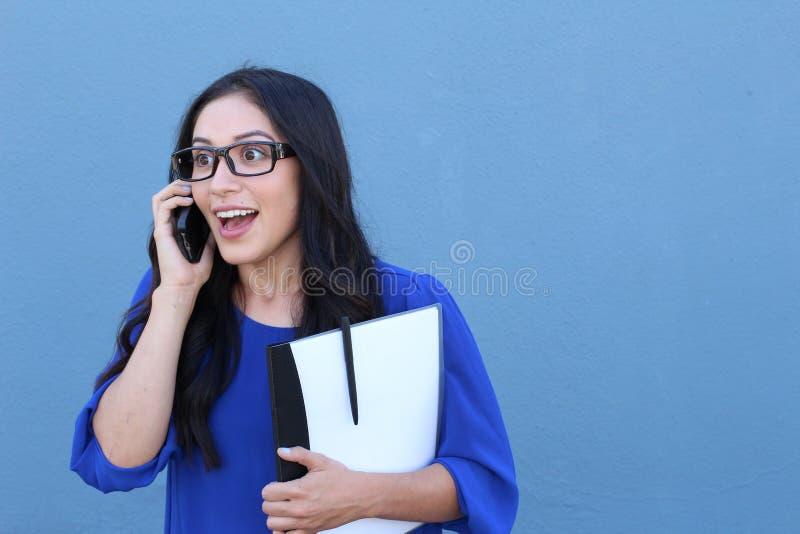 Emotionele verbaasde de celtelefoon van de onderneemsterholding op blauwe achtergrond royalty-vrije stock foto