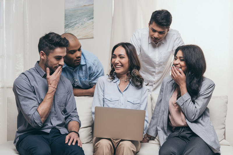 Emotionele vrienden die laptop met behulp van terwijl thuis het zitten op bank stock foto