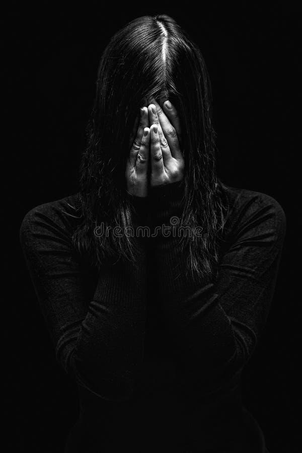 Emotionele vrouw die en het gezicht schreeuwen behandelen met de handen die de scheuren verbergen stock afbeelding