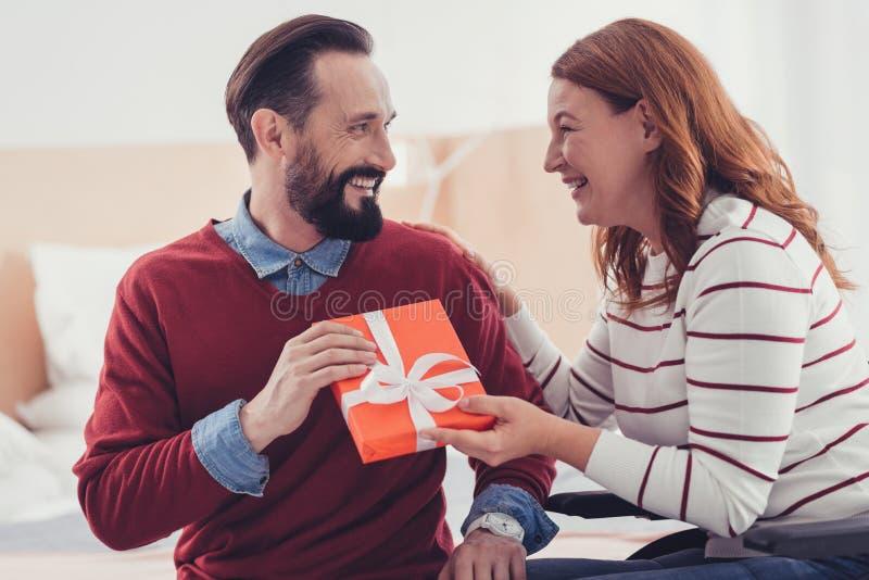 Emotionele vrouw die terwijl het geven van een heden aan haar gelukkige echtgenoot lachen royalty-vrije stock afbeelding