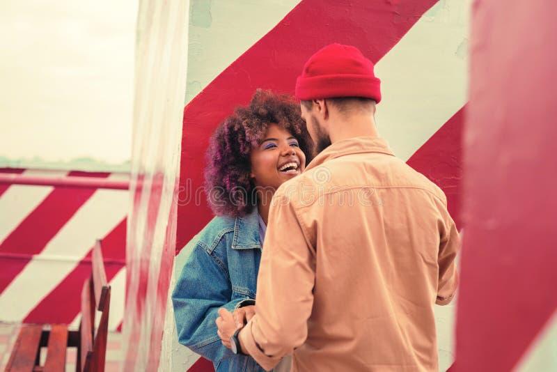 Emotionele vrouw die terwijl het houden van handen met haar jonge vriend lachen royalty-vrije stock afbeelding