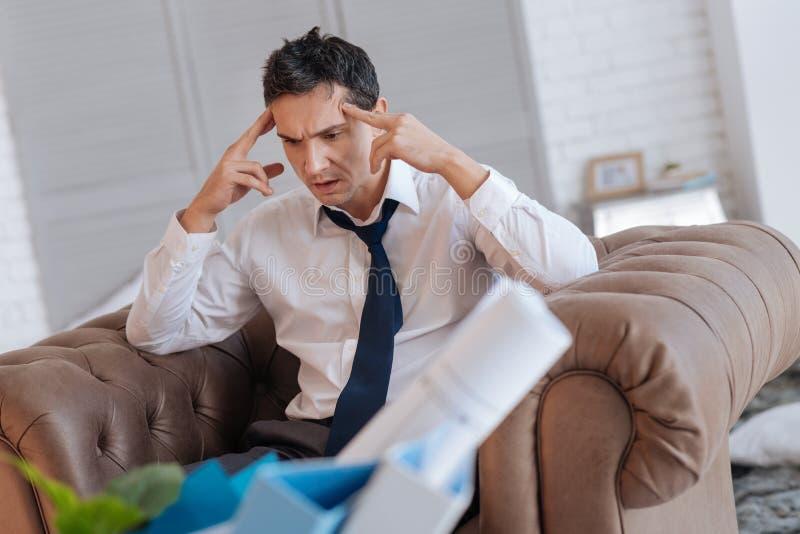 Emotionele werkloze mens die gek terwijl thuis het zitten gaan stock afbeelding