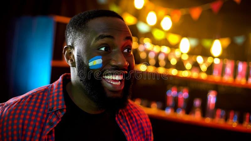 Emotionele zwarte voetbalventilator met Argentijnse vlag op wang het glimlachen het letten op TV royalty-vrije stock foto's