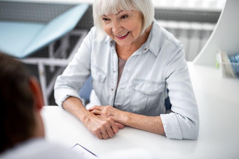 Emotionell åldrig dam som sitter på tabellen och le royaltyfri foto