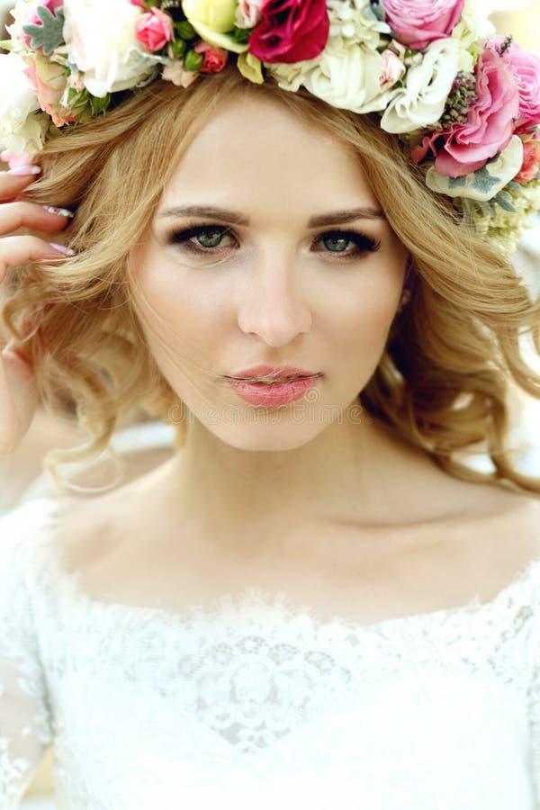 Emotionell berörd härlig blond brud i den vita klänningen i wreat royaltyfri fotografi