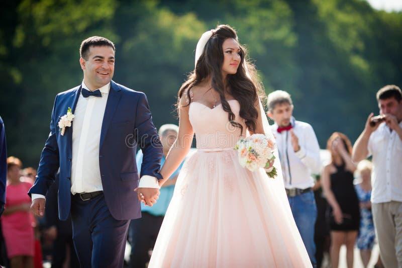 Emotionell brud med en bukett och lycklig brudgum som går till oss arkivbild