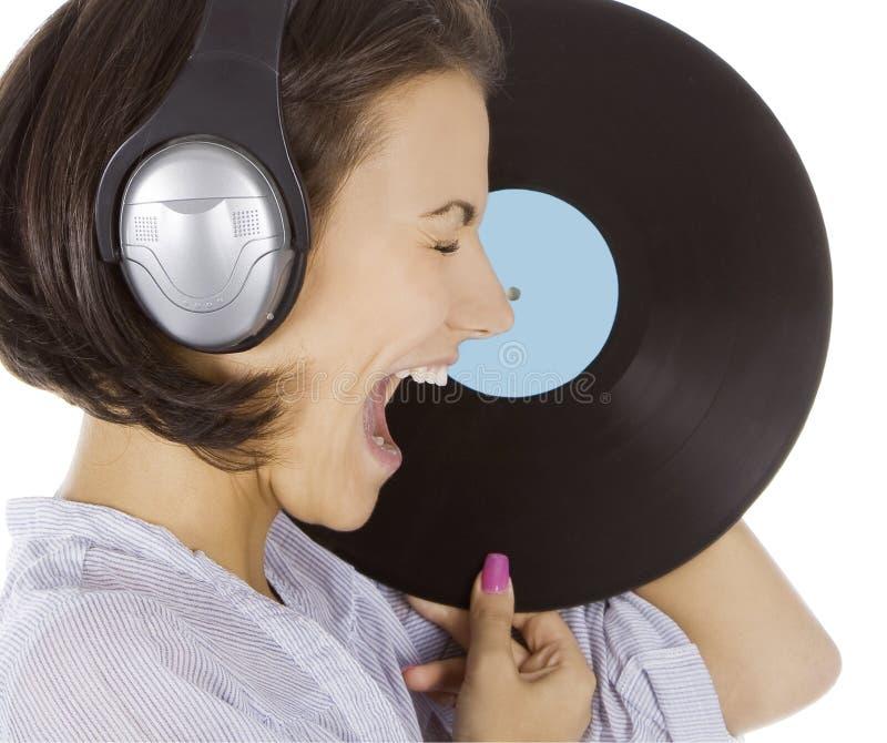 Emotionell brunett i hörlurar med vinylrekordet ov arkivbilder