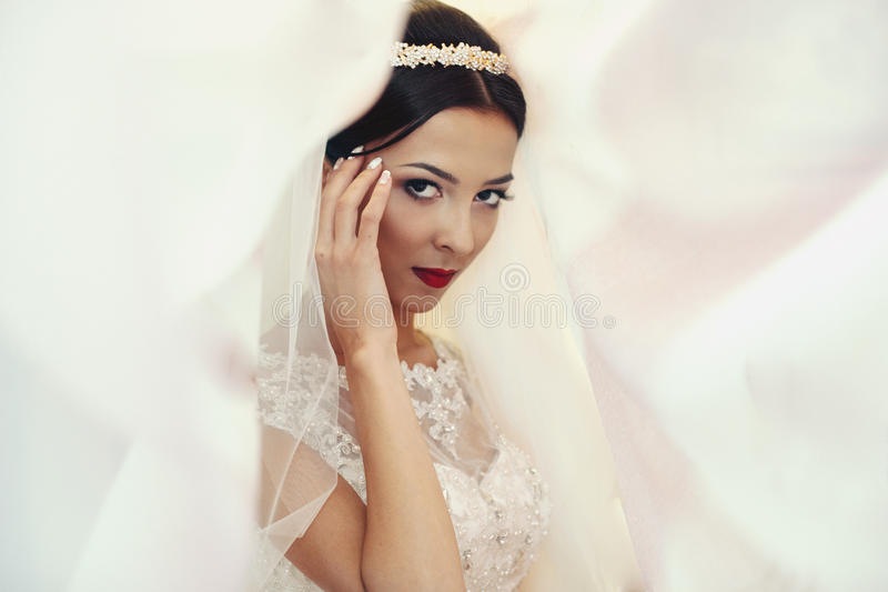 Emotionell brunettbrud i den vita klänningen för tappning som poserar under byracka arkivbilder