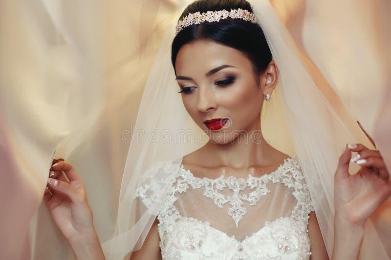 Emotionell brunettbrud i den vita klänningen för tappning som poserar under byracka royaltyfria foton