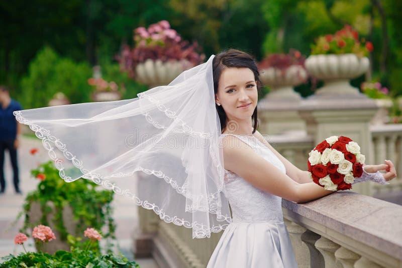 Emotionell brunettbrud i den vita klänningen som poserar på den near stenräcket för balkong royaltyfria bilder