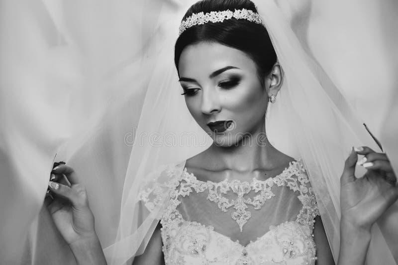 Emotionell brunettbrud i posera för klänning för tappning vitt arkivfoto