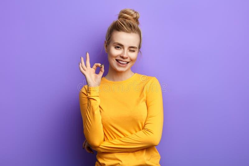 Emotionell charmig kvinna som visar det ok tecknet med fingrar och att blinka royaltyfria bilder