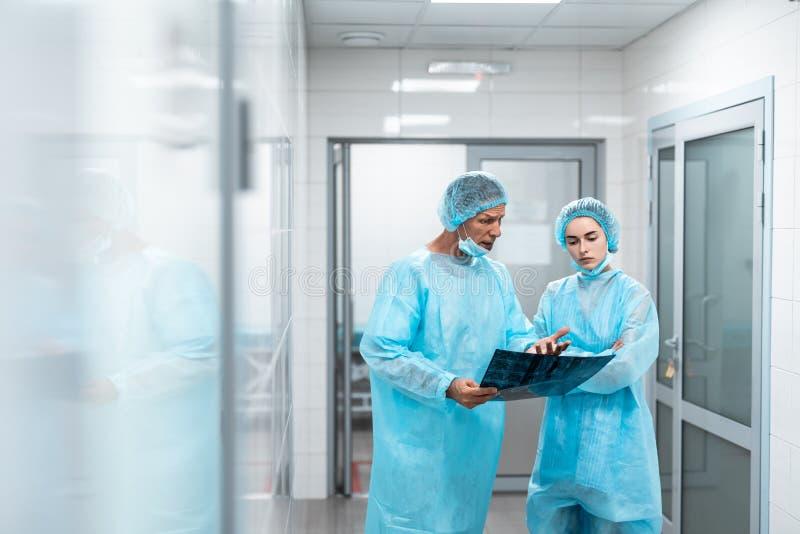 Emotionell doktor som rymmer röntgenstrålen och talar till hans kollega royaltyfri foto
