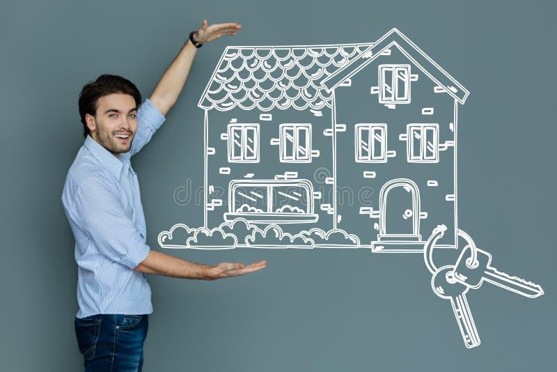 Emotionell fastighetsmäklare som ler, medan erbjuda ett stort härligt hus royaltyfri foto