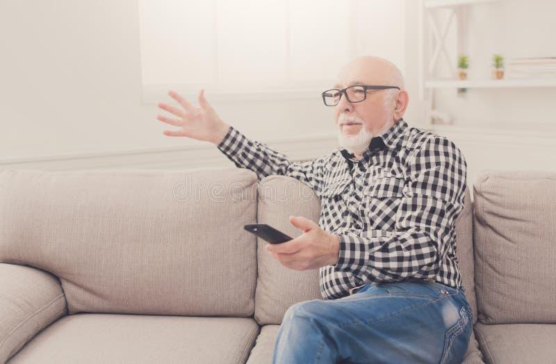 Emotionell hållande ögonen på tv för hög man att kopiera utrymme royaltyfria foton