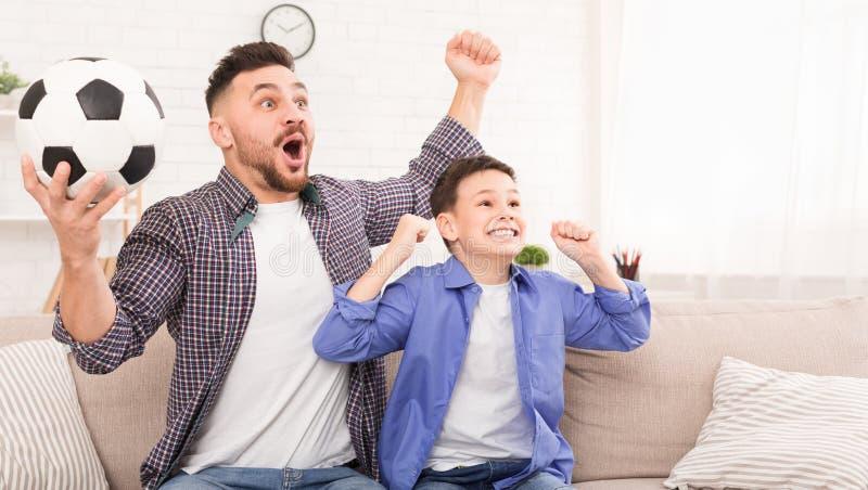 Emotionell hurra fotboll för fader och för son med fotbollbollen royaltyfri foto