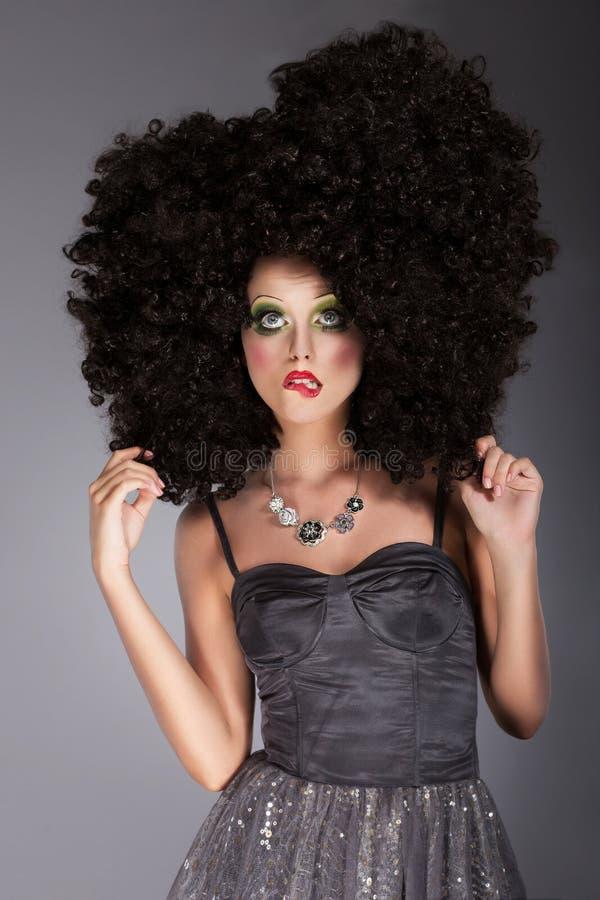 Emotionell kvinna i burrig peruk med flätade hår arkivbilder