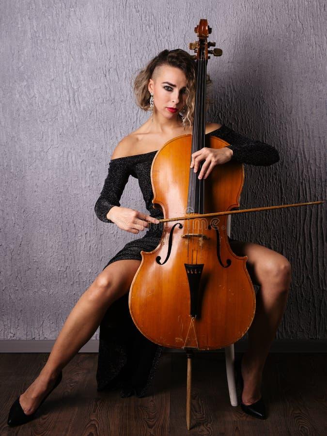 Emotionell kvinna i en aftonklänning som spelar violoncellen arkivfoto