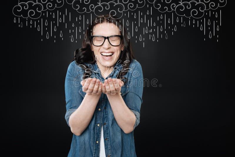 Emotionell kvinna som stänger henne ögon, medan fångas i regnet arkivfoto