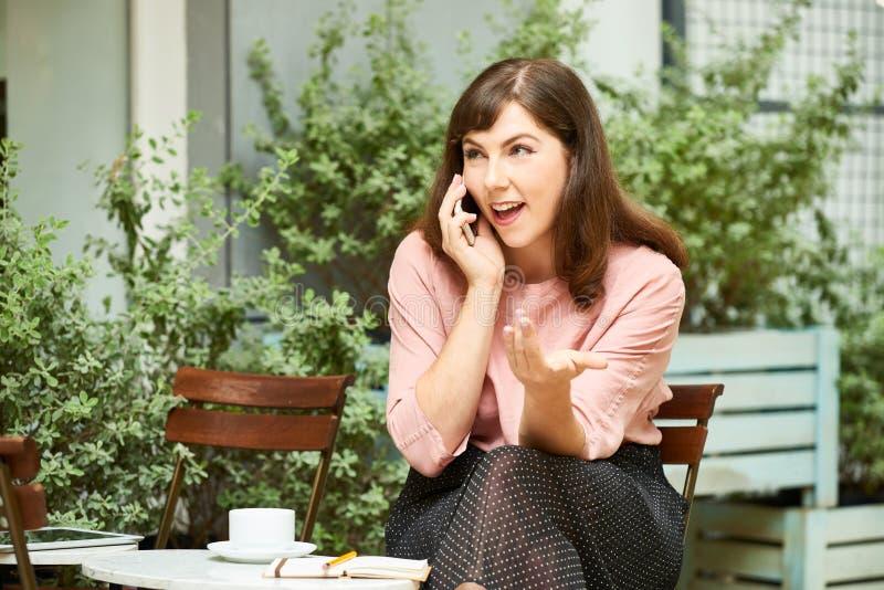 Emotionell kvinna som talar på telefonen royaltyfria bilder