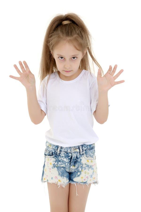Emotionell liten flicka i en ren vit T-tröja arkivfoto