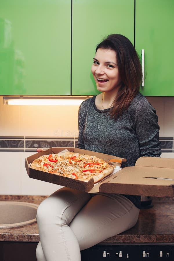 Emotionell lycklig flicka som rymmer italiensk pizza i pappers- öppnad ask royaltyfri bild