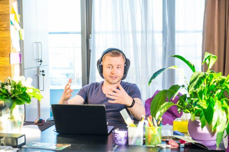 Emotionell man i hörlurar som ser datorskärmen, gester och deltar i online-mötet, konferens med affärsmedeltal royaltyfri fotografi