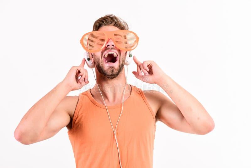 Emotionell man med lyssnande musik f?r h?rlurar lyssnande musik för orakad man i hörlurar med mikrofon den sexiga muskulösa manne arkivfoton