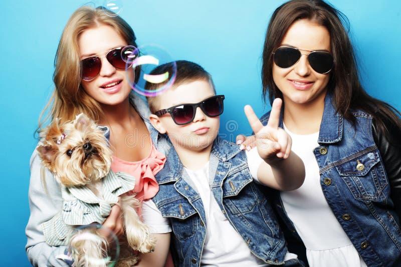 Emotionell och folkbegrepp för livstil, för lycka: systrar för broderans två, med slut för liten hund upp fotografering för bildbyråer