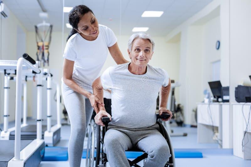 Emotionell rörelsehindrad pensionär som ler, medan sitta i hans rullstol royaltyfri fotografi