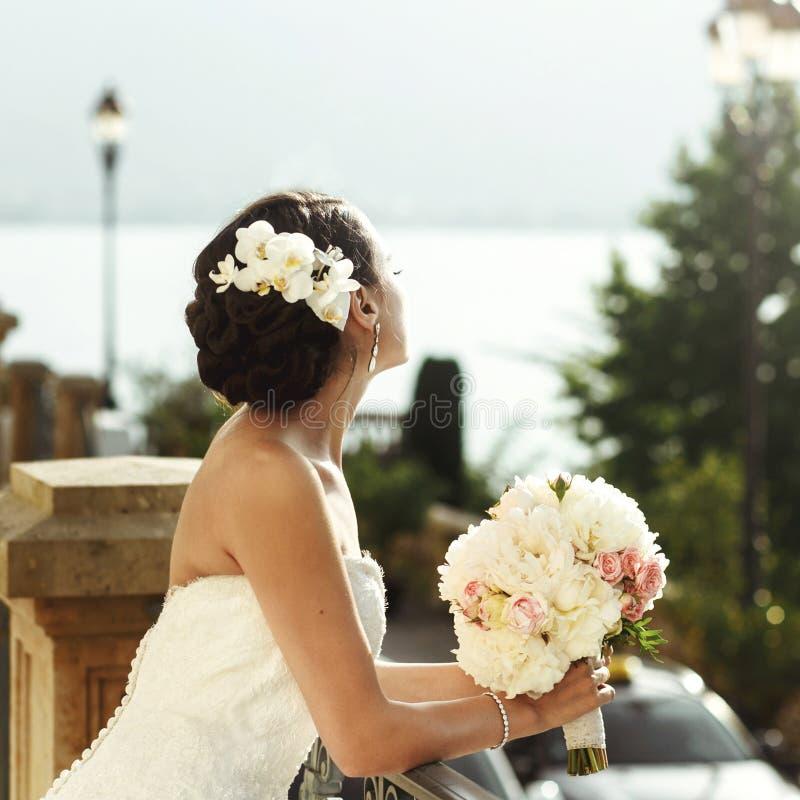 Emotionell sexig brunettbrud i den vita klänningen som poserar på balkong n arkivfoton